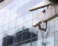 De witte camera van kabeltelevisie op voorzijde van de glasbouw Royalty-vrije Stock Foto
