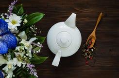 De witte ceramische theepot en het boeket van de lente bloeien op een houten achtergrond, concept feestelijke samenstelling, vrij Stock Afbeeldingen