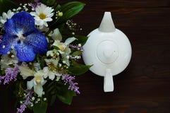 De witte ceramische theepot en het boeket van de lente bloeien op een houten achtergrond, concept feestelijke samenstelling, vrij Stock Foto