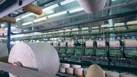 De witte die draden worden mechanisch onder spoelen opnieuw worden gevestigd Textielfabrieksmateriaal stock footage