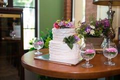 De witte die 2 tiered huwelijkscake met roze en sering wordt verfraaid bloeit op de bovenkant Traditionele Witte Huwelijkscake Op Royalty-vrije Stock Foto's