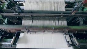 De witte doek wordt geproduceerd op een industrieel weefgetouw stock video