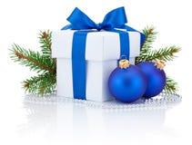 De witte doos bond blauwe lintboog, de tak van de pijnboomboom en twee die Kerstmisballen op wit wordt geïsoleerd Stock Foto's