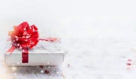 De witte doos van de Kerstmisgift met rode boog op sneeuw met bokeh en sneeuwval, banner royalty-vrije stock afbeelding