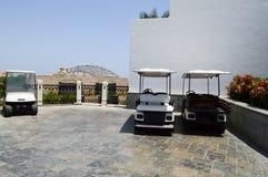 De witte elektrische golfauto's worden geparkeerd in kleine elektrische voertuigen met het afbaarden van de zon in warme tropisch stock foto's
