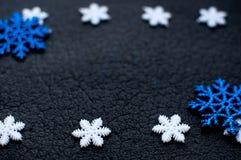 De witte en blauwe decoratie van Kerstmissneeuwvlokken op zwarte geweven achtergrond Royalty-vrije Stock Foto