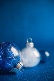 De witte en blauwe Kerstmisornamenten op donkerblauw schitteren achtergrond met ruimte voor tekst Stock Afbeeldingen