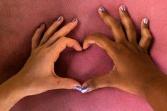 De witte en zwarte handen van meisjes vormen een hart van vingers tegen racisme stock fotografie