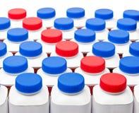 De witte flessen met rode en blauwe plastic dekking met zuivelfabriek draaiden ook zure zuivelproducten op een witte achtergrond Royalty-vrije Stock Foto