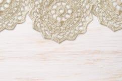 De witte geschilderde houten raad en haakt doilies Stock Fotografie
