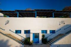 De witte Griekse bouw met blauwe vensters royalty-vrije stock fotografie