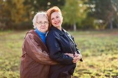 De witte haired bejaarde moeder koestert volwassen dochter royalty-vrije stock foto