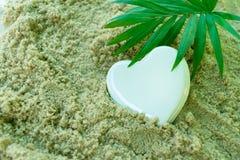 De witte hart en palmtak, ligt op het overzeese zand Het concept een de zomervakantie royalty-vrije stock afbeelding