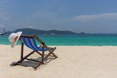 De witte hoed ligt op de rand van de chaise-longue, de kust met een mooie mening stock fotografie