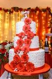De witte huwelijkscake met drie verdiepingen met rode bloemen Stock Afbeeldingen