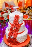 De witte huwelijkscake met drie verdiepingen met rode bloemen Stock Fotografie