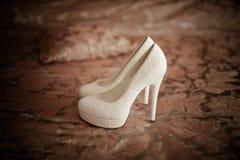 De witte huwelijksschoenen liggen op het bed Royalty-vrije Stock Foto's
