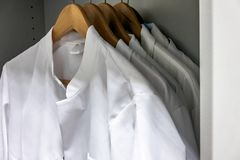 De witte kielen op houten hangers hangen in de kast van een laboratorium royalty-vrije stock foto's