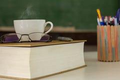 De witte koffiekop wordt geplaatst op het boek stock afbeelding