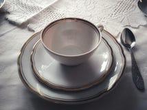 De de witte kop en schotel van de porseleinthee op een wit tafelkleed Tea Party-Ceremonie royalty-vrije stock afbeelding