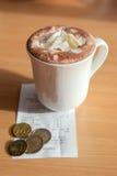 De witte kop van hete chocolade met rekening en euro muntstukken Stock Foto's