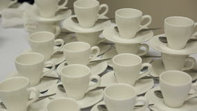 De witte koppen met schotels en theelepeltjes zijn op lijst in verscheidene rijen bij banket stock footage