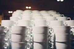 De witte koppen voor koffie en thee stapelden zich op uitstekende lijst dicht bij venster open aan tuingebied op royalty-vrije stock foto's