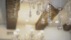 De witte kristalkroonluchters hangen op plafond in zaal binnen stock video
