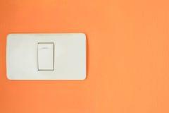 De witte lichte schakelaar, zet of doet de lichten op de oranje muur aan uit Stock Afbeeldingen