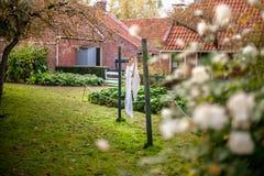 De witte linnenwasserij hangt op oude drooglijn met polen in een tuin met gras en bloeiende bloemen stock afbeelding