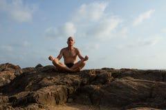 De witte man mediteert op de bovenkant van de oude klip stock fotografie