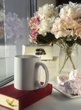 De witte mok op het rode boek, heemst, hydrangea hortensia bloeit dichtbij het venster in zonlicht stock foto