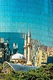 De witte moskee met een hoge minaret dacht in de glasoppervlakte na van een moderne wolkenkrabber in Baku, Azerbeidzjan Royalty-vrije Stock Afbeelding
