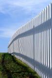 De witte Omheining van het Piket over Blauwe Hemel en Groen Gras Stock Fotografie