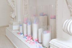 De witte open haard is verfraaid met kaarsen en bloemen stock foto's
