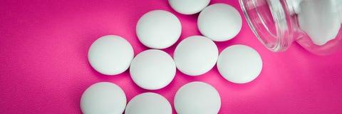 De witte pillen zijn verspreid van een glasfles op een roze achtergrond vignetting royalty-vrije stock fotografie