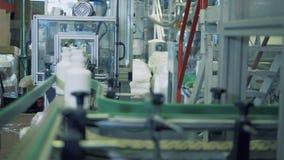 De witte plastic containers bewegen zich langs de vervoerder stock video