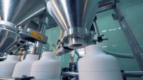 De witte plastic kruiken worden die door de machine worden gevuld stock videobeelden