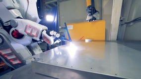 De witte robot gebruikt een lassenhulpmiddel, omhoog sluit De speciale robotwerken bij een installatie, lassende metaalbladen stock footage