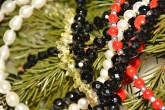 De witte, rode, zwarte, groene en gele parels op een naaldboom vertakken zich Royalty-vrije Stock Afbeelding