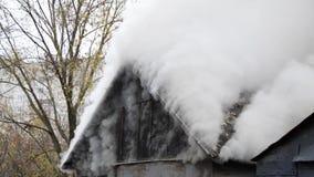 De witte rook komt uit het brandende dak van het huis stock footage
