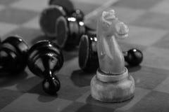 De witte schaakridder veegde door het leger van vijandelijke panden op een oud gekrast schaakbord Spoedaanval Het zwarte Leger wo royalty-vrije stock foto's