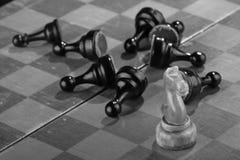 De witte schaakridder veegde door het leger van vijandelijke panden op een oud gekrast schaakbord Spoedaanval Het zwarte Leger wo stock foto