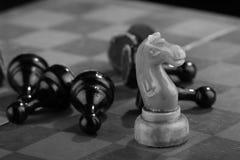 De witte schaakridder veegde door het leger van vijandelijke panden op een oud gekrast schaakbord Spoedaanval Het zwarte Leger wo royalty-vrije stock foto