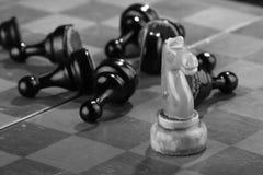 De witte schaakridder veegde door het leger van vijandelijke panden op een oud gekrast schaakbord Spoedaanval Het zwarte Leger wo royalty-vrije stock afbeelding