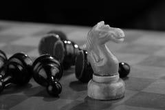 De witte schaakridder veegde door het leger van vijandelijke panden op een oud gekrast schaakbord Spoedaanval Het zwarte Leger wo stock fotografie