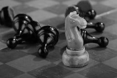De witte schaakridder veegde door het leger van vijandelijke panden op een oud gekrast schaakbord Spoedaanval Het zwarte Leger wo royalty-vrije stock fotografie