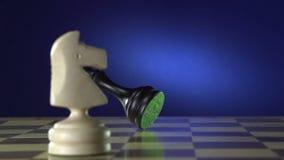 De witte schaakspeler haalt de zwarte koning met zijn stuk neer stock videobeelden