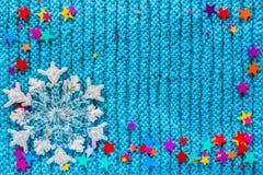 De witte sneeuwvlok en de veelkleurige sterren op een blauw breien achtergrond Royalty-vrije Stock Foto's