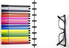 De witte spatie sketchbook met van het kleurenpen en oog glazen voor bedrijfsmalplaatje, Hoogste Mening/Vlak legt Stock Foto's